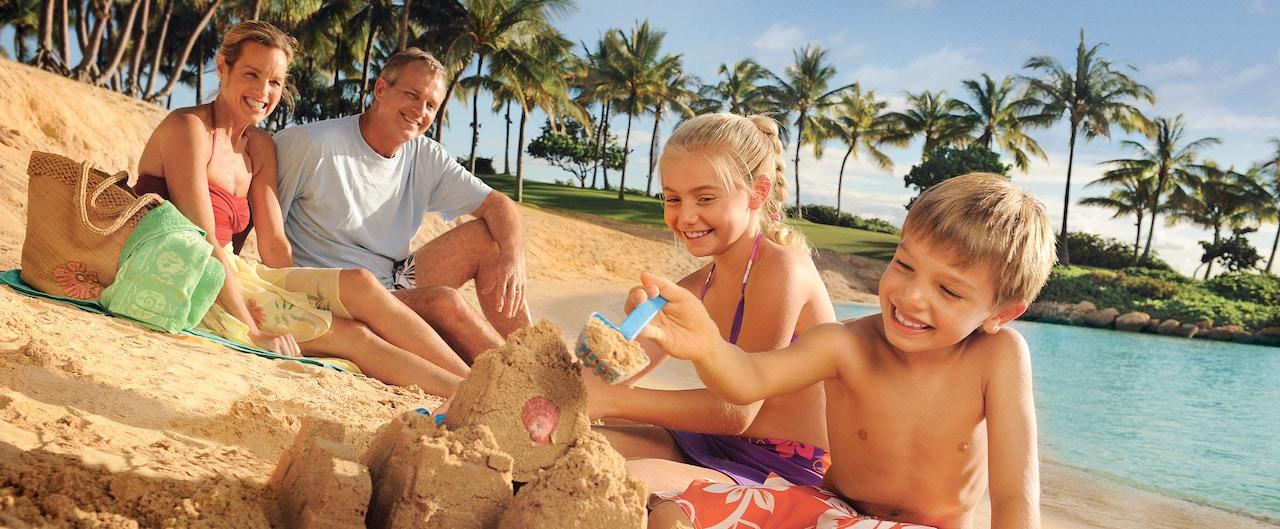 Children build a sand castle on the Aulani beach