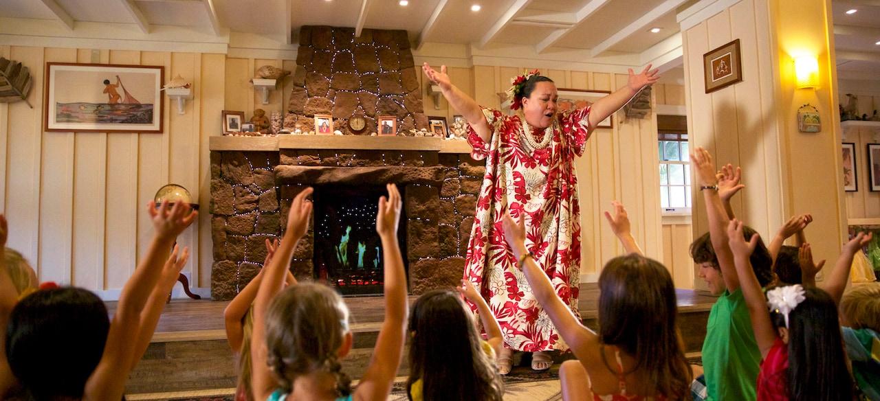 ハワイ風の服装で両手を高く上げるアンティと、床に座ってそれを真似する子供たち