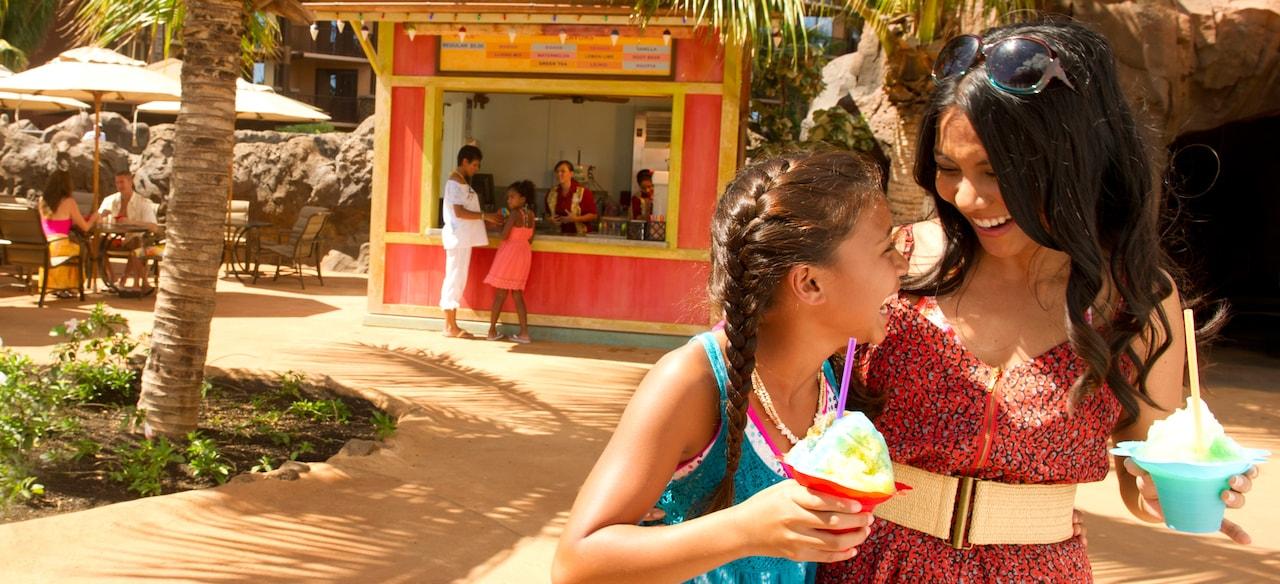 カラフルな近くのお店からシェイブアイス・デザートを買って楽しむ母親と娘
