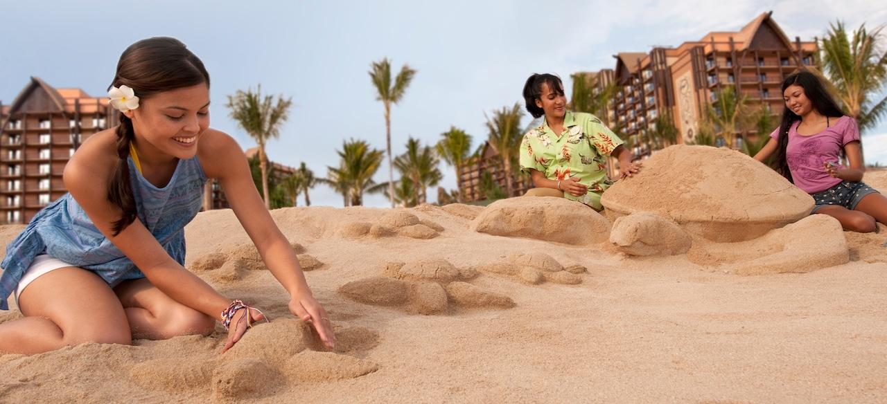 キャストメンバーの指示の下、砂で大小の 3D のカメの像を作る 2 人の少女
