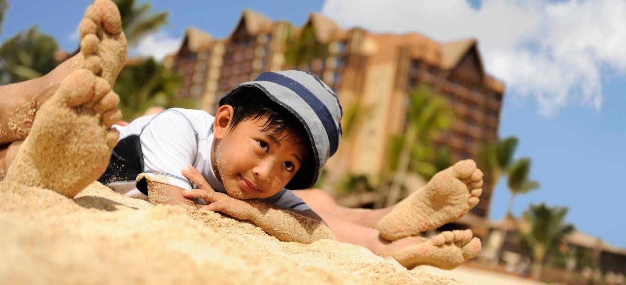 2 組の砂にまみれた足の間で、砂浜に寝そべって物思いにふける少年