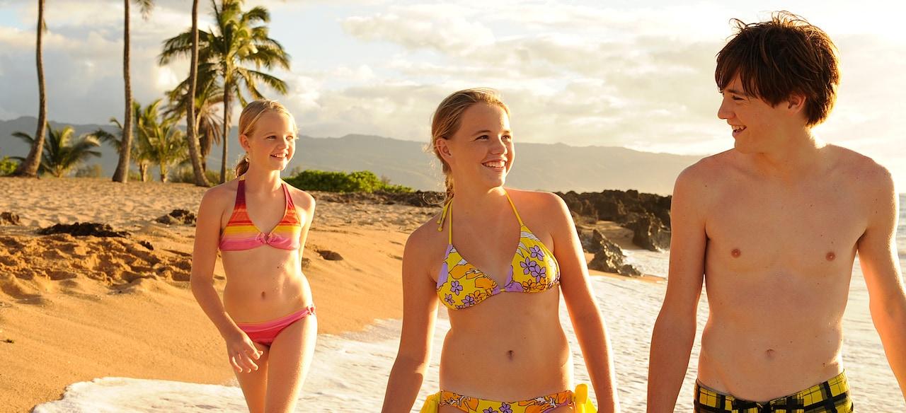 南国のビーチを歩く水着の少年と少女と、そのすぐ後ろをついて歩く別の少女