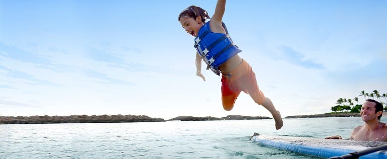 A boy in a life jacket leaps off a surfboard, hanging in midair over the ocean as his father watches