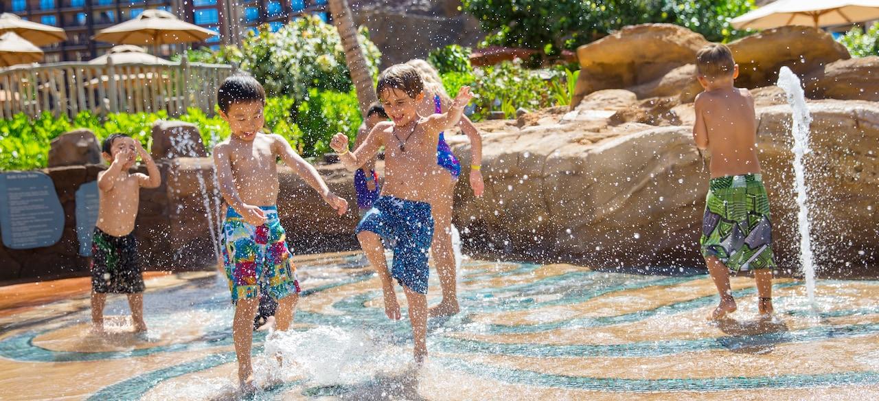 舗装エリアで、噴き上がるウォーター・ジェットではしゃぐ海水パンツをはいた 2 人の少年と、さらに 4 人の子供たち