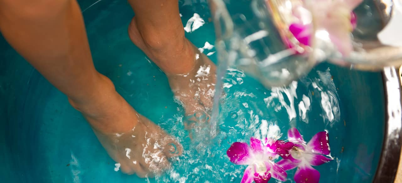フクシア蘭が浮かべられた、水が注ぎ込まれている大きな水盤に浸した足