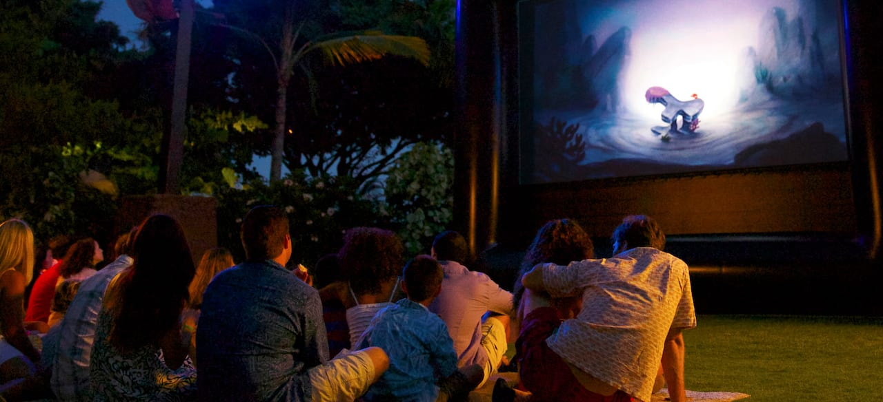 Families sitting outside on the grass after dark, watching an animated film on a projection screen