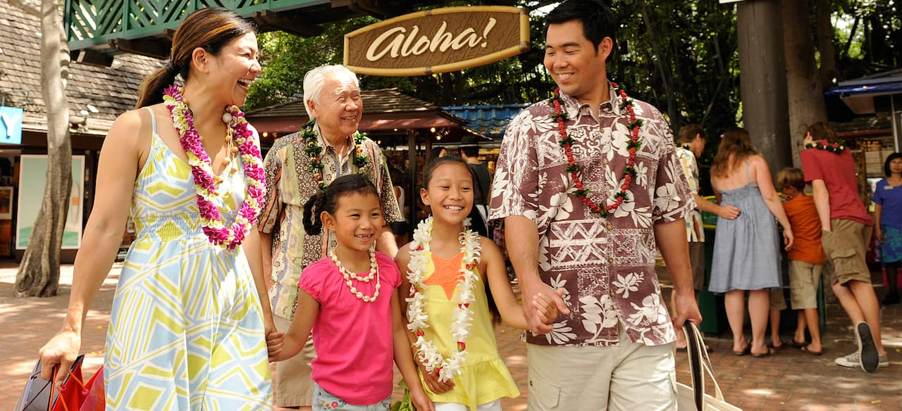 A mother, father, 2 girls and a grandfather in island attire stroll along an outdoor shopping promenade