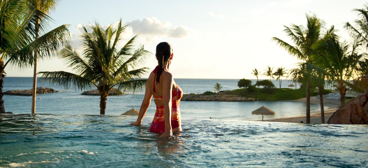 ジャグジーから海と空の風景を見つめる水着の女性