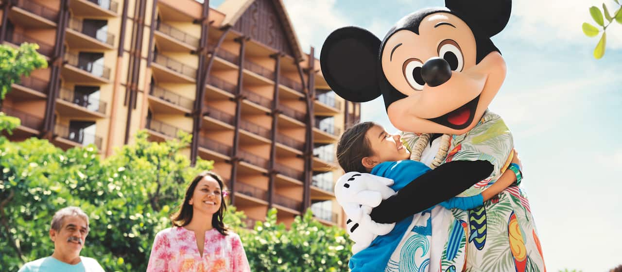 Mickey Mouse, dressed in an Aloha shirt and shell lei interacts with a young woman in front of the Aulani Resort