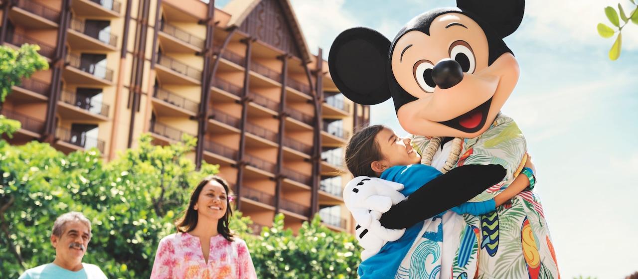アロハシャツを着て貝殻のレイを付けたミッキーマウスが、アウラニ・リゾートの前で若い女性とやりとりをしている場面
