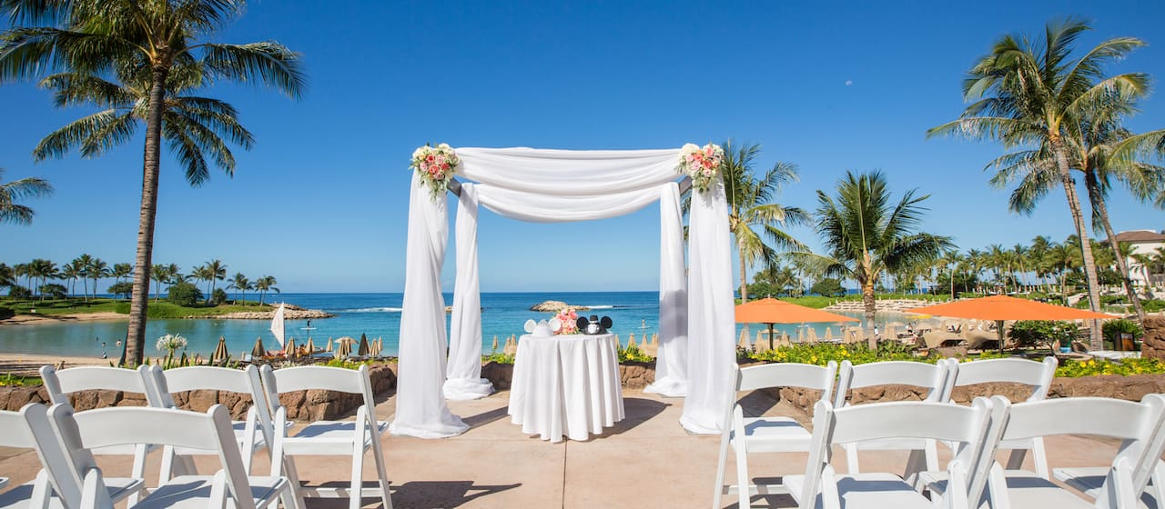 An Aulani Resort outdoor courtyard area overlooking the ocean is dressed for a wedding with an altar and folding chairs