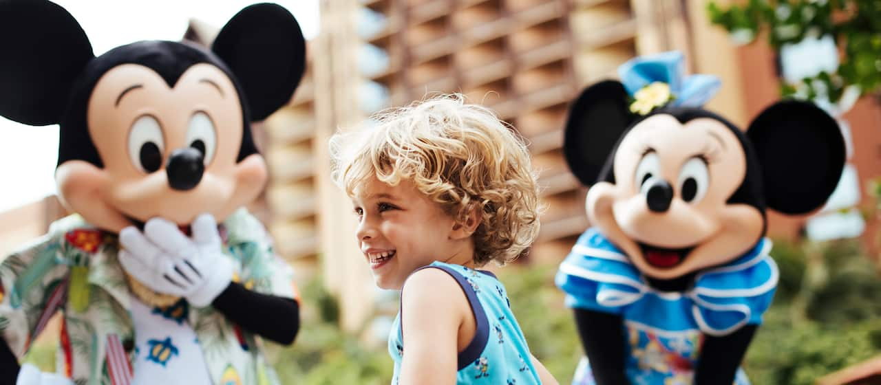 A young boy dances as Mickey Mouse and Minnie Mouse look on