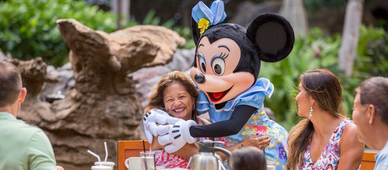 Minnie Mouse hugs a smiling woman who is seated at breakfast table as her family looks on