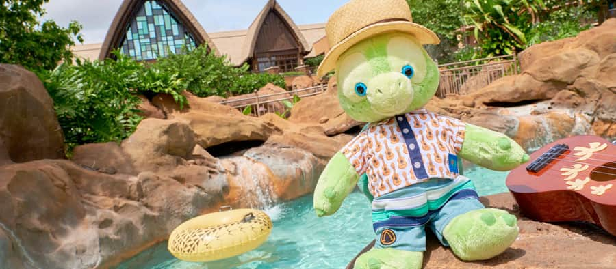An Olu the Turtle plush toy sits on a rock with a ukulele near the Waikolohe Stream at Aulani Resort