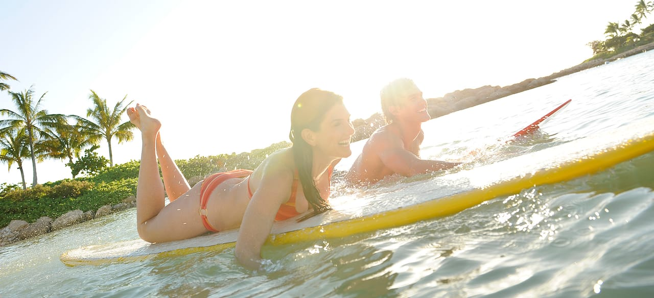 A young woman and man lie on their bellies paddling surfboards in a lagoon