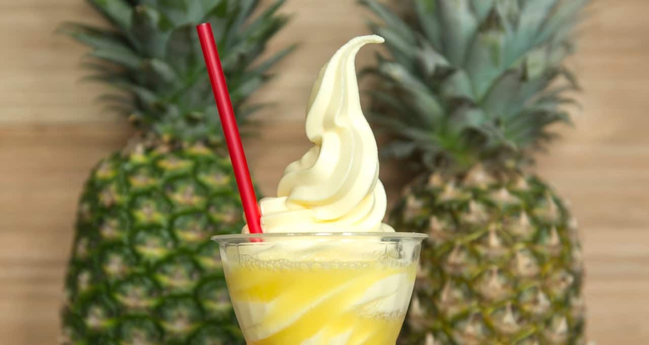 A swirl of soft serve ice cream in a cup with a straw is flanked by 2 pineapples