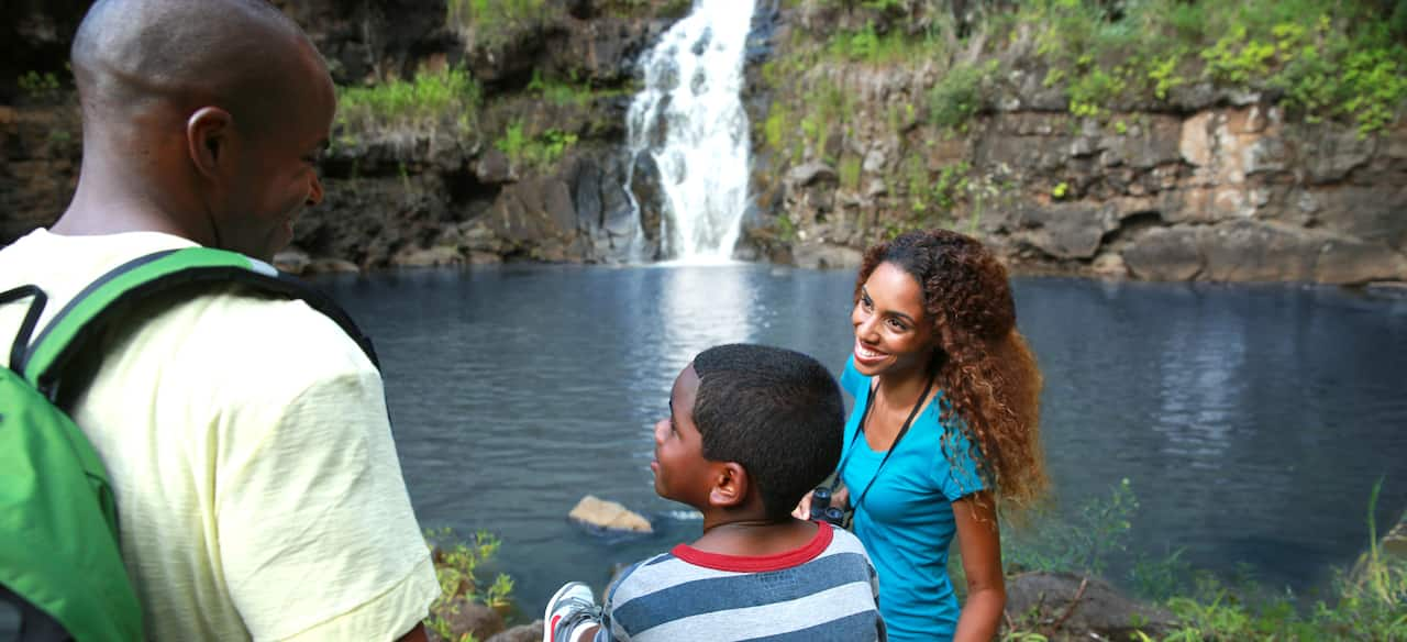 A man and woman with a boy at a pond being fed by a waterfall