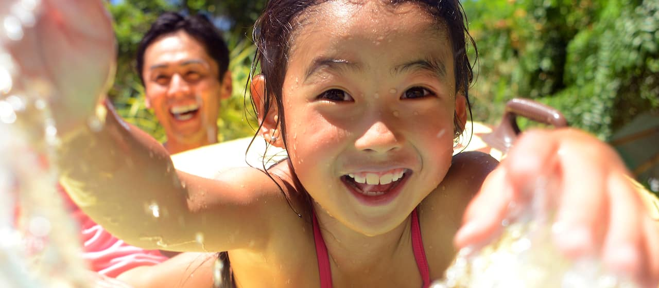 A laughing young girl wet from splashing rides an inflated tube as his father looks on laughing behind her.