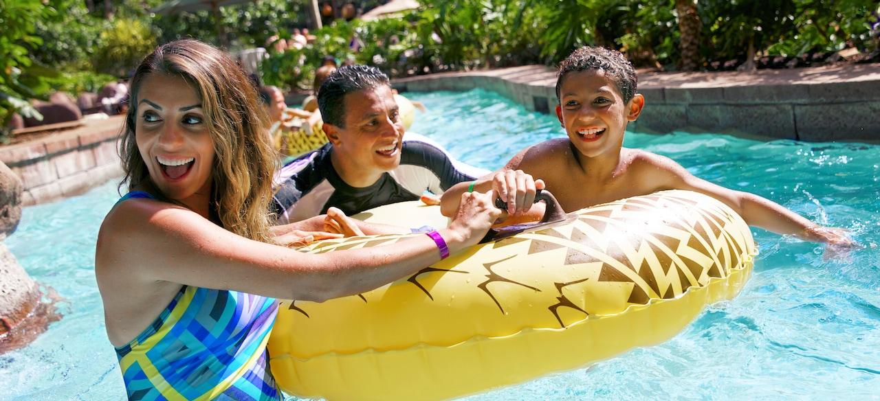 流れるプールを下りながら浮き輪につかまって笑顔を見せる両親とその息子