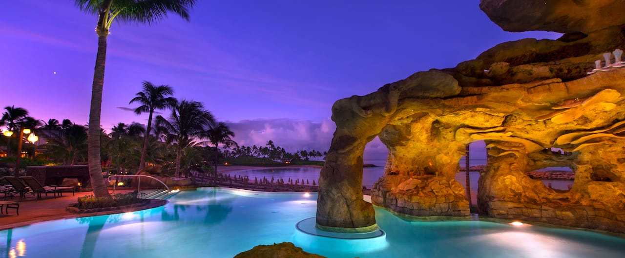 Evening lights illuminate the Ka Maka Grotto oceanfront pool while the sun sets