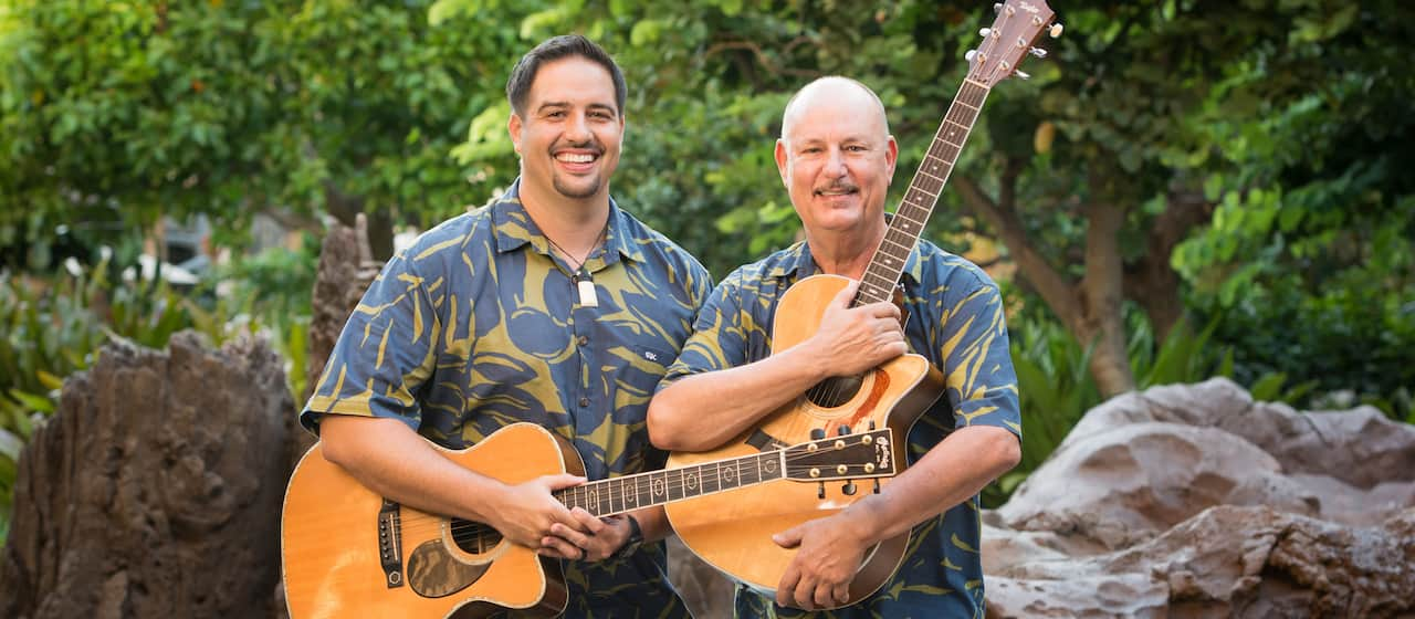 Singer/songwriter Jerry Santos holds his guitar and stands beside Kamuela Kimokeo, both wearing matching Aloha shirts