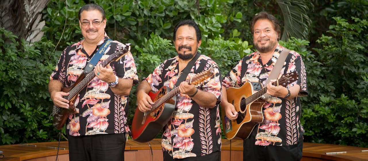 The Makaha Sons, Jerome Koko, Kimo Artis and Mark Yim play their guitars while wearing matching Aloha shirts