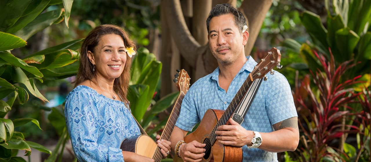 Musical duo Shawn Imental and Lehua Kalima, both with flowers behind their ears, hold their guitars while standing in front of some plants