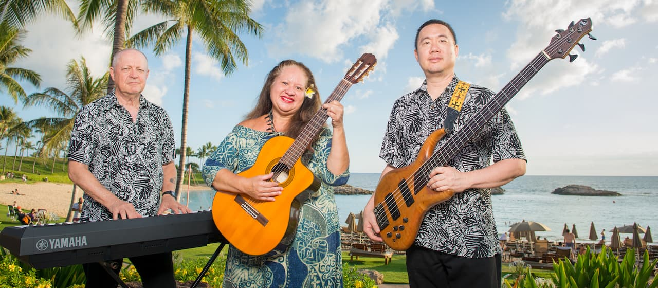 Musician Teresa Bright holds her guitar and stands between her keyboard player and bass player with the Pacific Ocean behind them