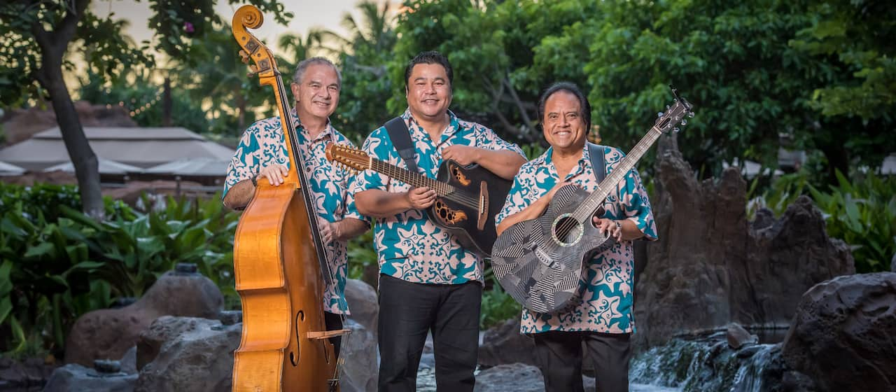 The members of Ho'okena, Horace K. Dudoit III, Chris Kamaka and Glen H.K. Smith, hold their instruments while standing in front of a koi pond in matching Aloha shirts
