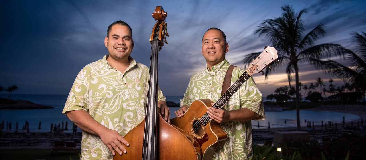Kaulalua members, Kanai'a Nakamura and Dennis Keohokālole, wear matching Aloha shirts and pose with a standup bass and guitar in front of Ko Olina Beach