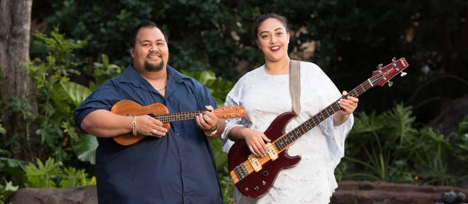 Wayne Kane, also known as Kekoa Kane, holds a 'ukulele while standing beside a woman holding a bass