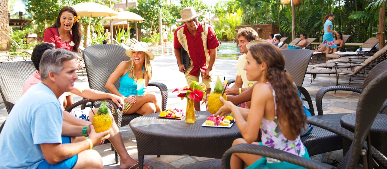Aulani Resort Guests enjoy tropical cocktails at a patio table by a pool surrounded by palm trees