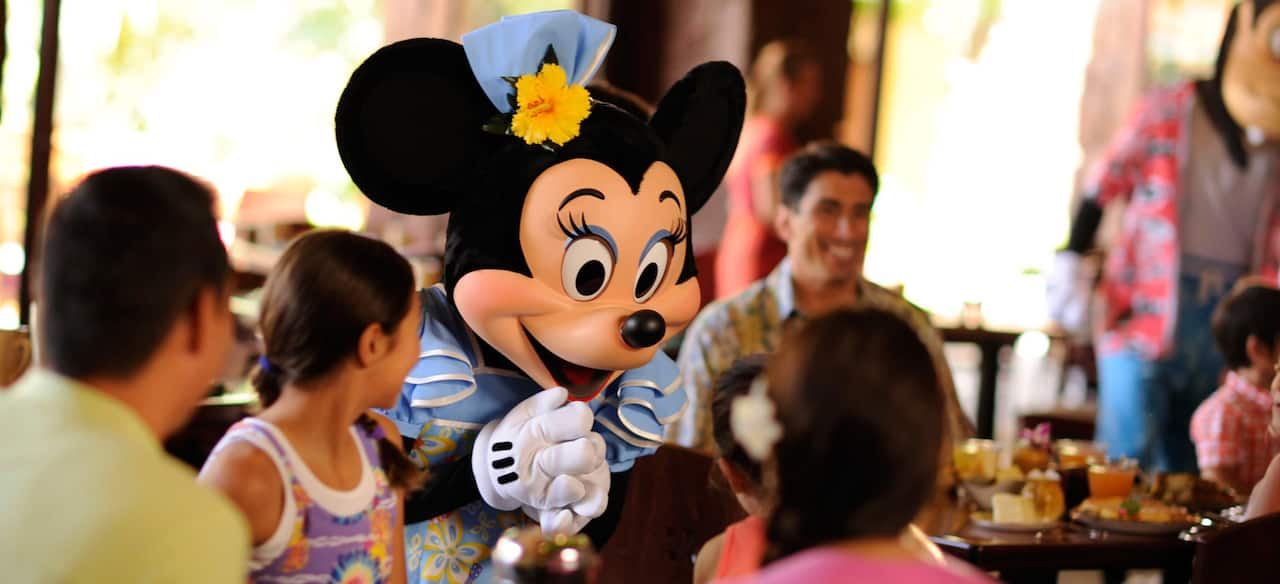 Minnie Mouse greets a family at the Character Breakfast at Aulani's Makahiki dining venue