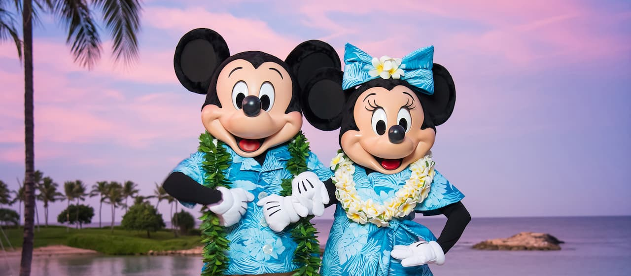 Mickey and Minnie, arm in arm, dressed Hawaiian style with leis, posing by the beach