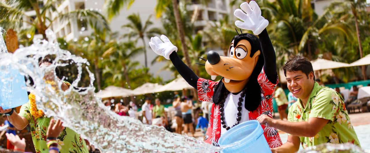 A Cast Member throws a bucket of water while Goofy waves his hands in the air