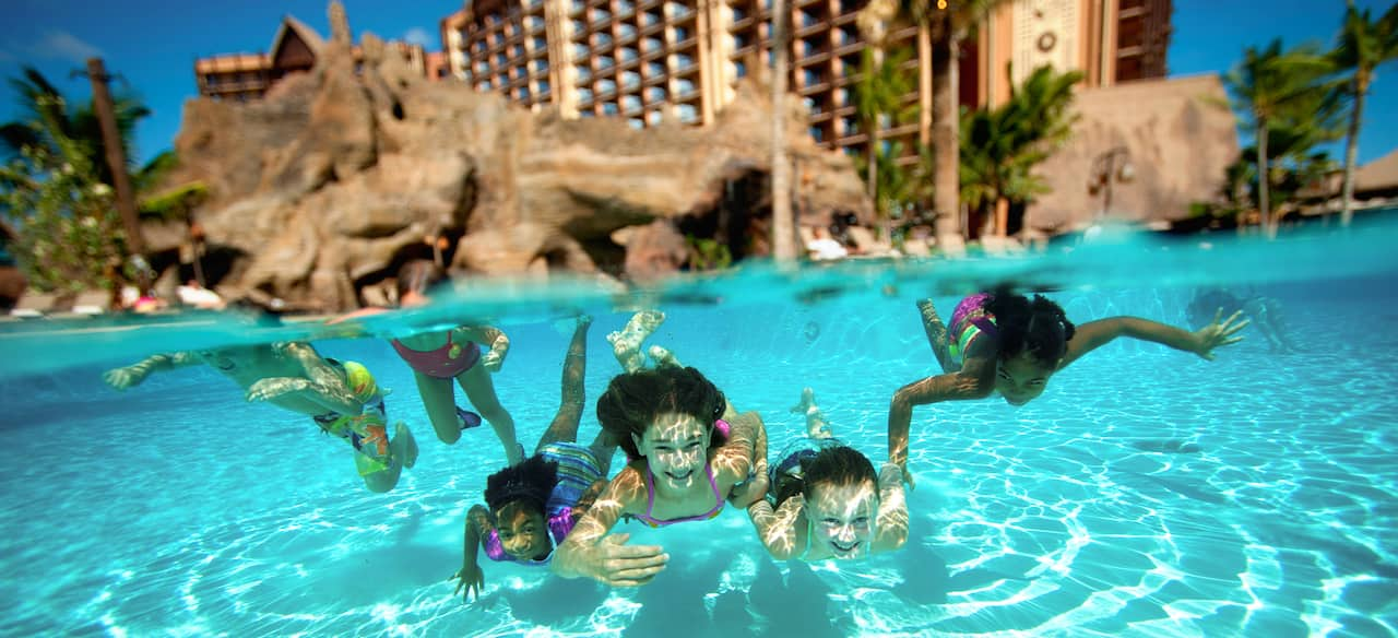 Four girls swim underwater together in a pool with rock caves and palm trees while a boy and girl paddle behind