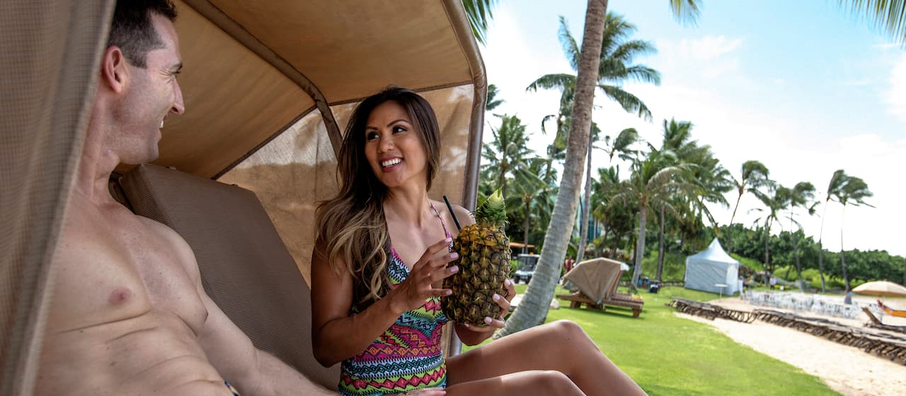 A smiling young woman holds a pineapple beverage while relaxing in a cabana with a smiling young man