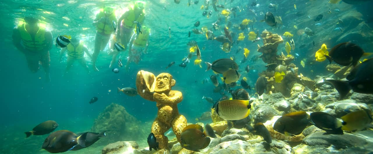 Guests discover a submerged Menehune statue as they snorkel atop the tropical waters of Rainbow Reef