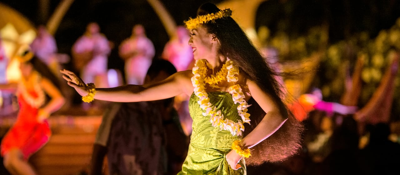 Woman adorned with leis dancing the hula