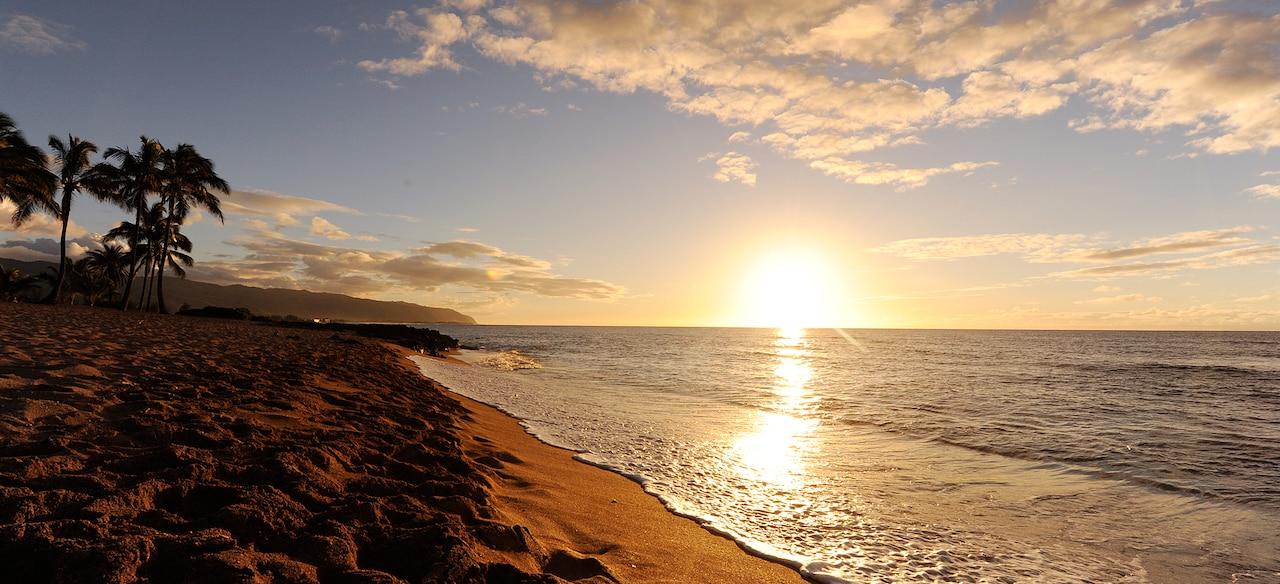 水平線に沈む夕陽と南国のビーチに打ち寄せる波