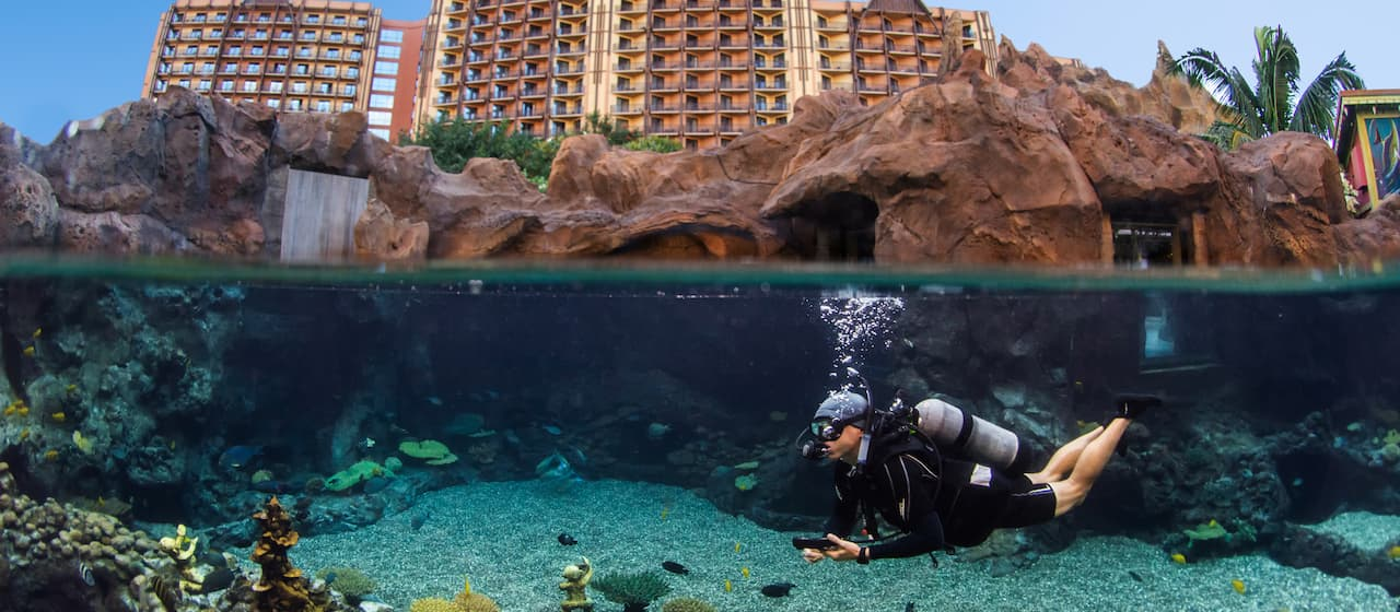 A man scuba dives at the Rainbow Reef lagoon at Aulani Resort