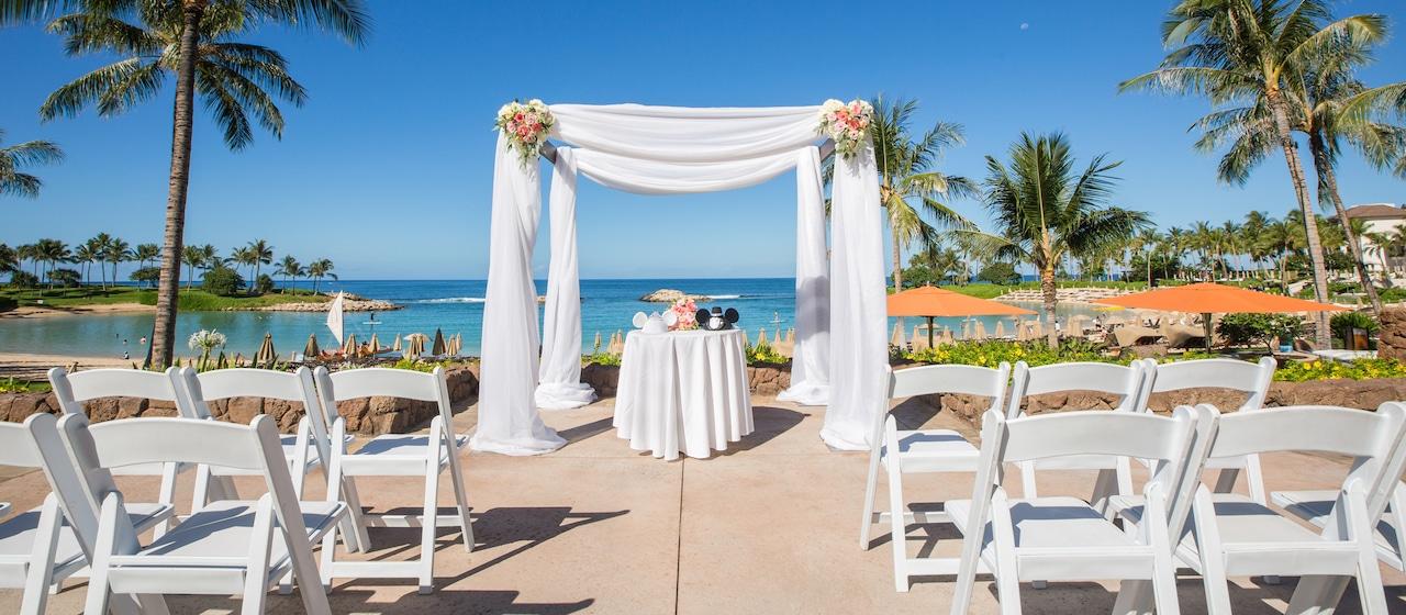 青い海をバックに挙式の椅子やテーブルなどのセッティングをされたアマアマ・パティオ