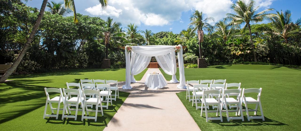 青空を背景にテーブルや椅子など挙式のセッティングをされた緑豊かなハラヴァイ・ローンに