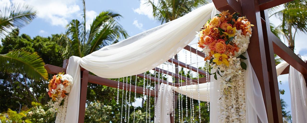 ウエディングフラワーやビーズ、ドレイプに飾られたアウトドアガゼボ