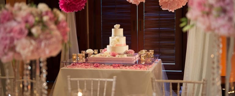 A white 3-tiered wedding cake on a table decorated with pink roses, scattered petals and votive candles