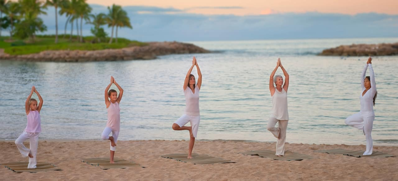 Two young girls and 3 women of various ages stand in tree pose in a yoga class on the beach