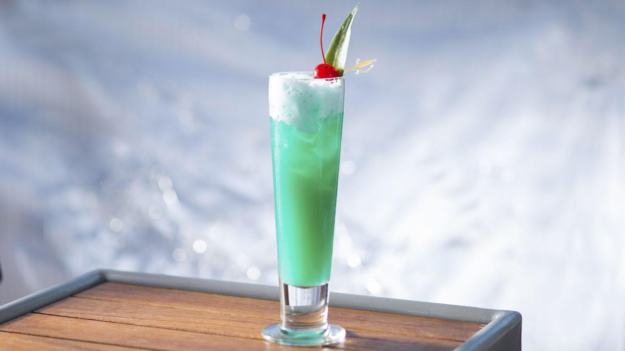 トールグラスにオンザロックで注がれたブルー・ハワイアンのカクテルに、マラスキーノ・チェリーとプラスチックの小さな剣に刺した葉っぱの飾りを添えて