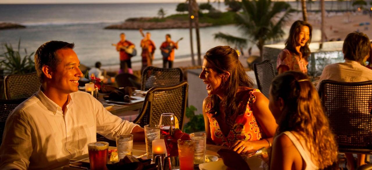 夕焼けのオーシャン・ビューとライブ・ミュージシャンを背景に屋外テーブルでドリンクを楽しむ家族