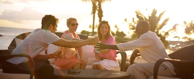 Two men and 2 women raise their cups in an enthusiastic toast at an outdoor table with an ocean view