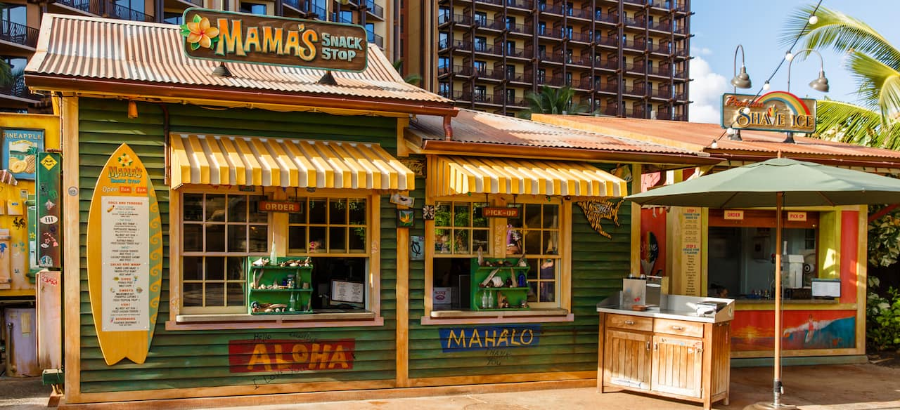 The exterior of Mama's Snack Stop, a quick-service venue with weathered green paint and yellow-striped awnings